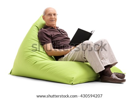 Relaxed senior man reading a book seated on a green beanbag isolated on white background - stock photo