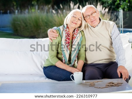 Relaxed senior man sitting with arm around woman on couch at nursing home porch - stock photo