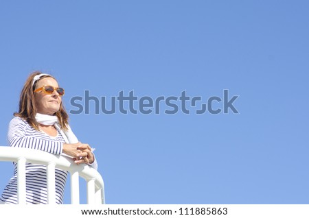 Relaxed senior woman enjoying lookout leaning at handrail, isolated with blue sky as background and copy space. - stock photo
