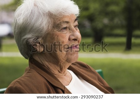Relaxed senior woman sitting on a bench in park - stock photo