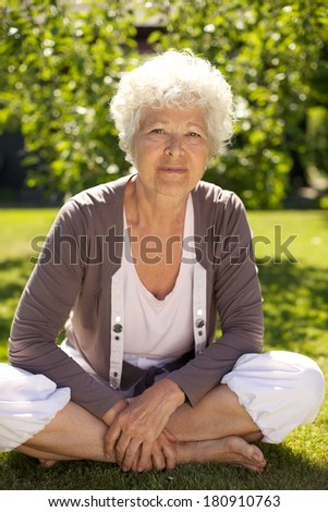 Relaxed senior woman sitting on grass with her legs crossed in garden outdoors - stock photo