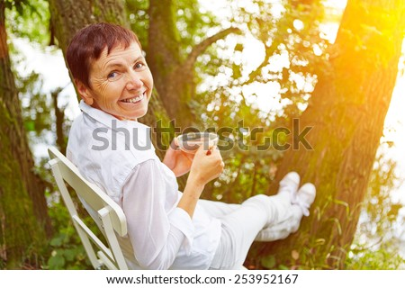 Relaxed senior woman taking a break with cup of tea in her garden - stock photo