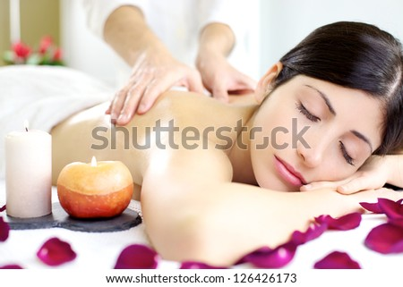 Relaxed sleeping beautiful woman getting massage from man in spa - stock photo