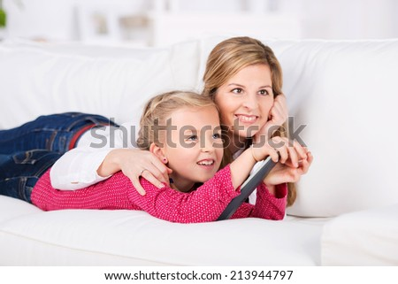 Relaxed smiling woman and kid with remote control lying on sofa at home - stock photo