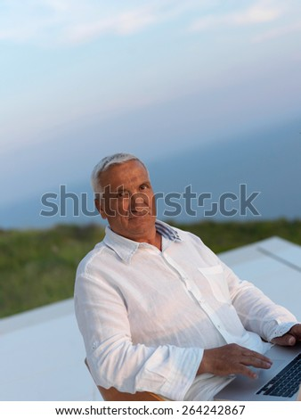 relaxed white hair senior man looking sunset from luxury balclony home and working on laptop computer - stock photo