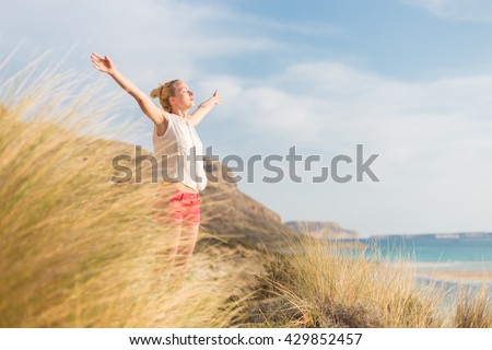 Relaxed woman, arms rised, enjoying sun, freedom and life an a beautiful beach. Young lady feeling free, relaxed and happy. Concept of vacations, freedom, happiness, enjoyment and well being. - stock photo