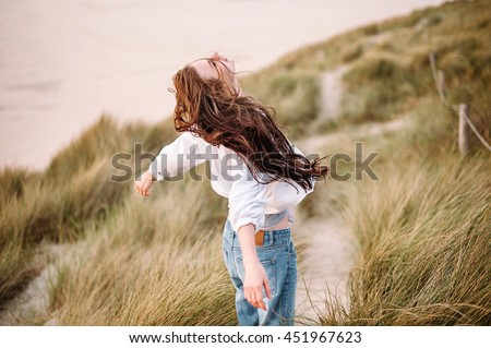 Relaxed woman, arms rised, freedom and life among a beautiful dunes. Young lady feeling free, relaxed and happy. Concept of vacations, freedom, happiness, enjoyment and well being. - stock photo