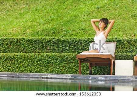 relaxed woman at poolside, bali - stock photo
