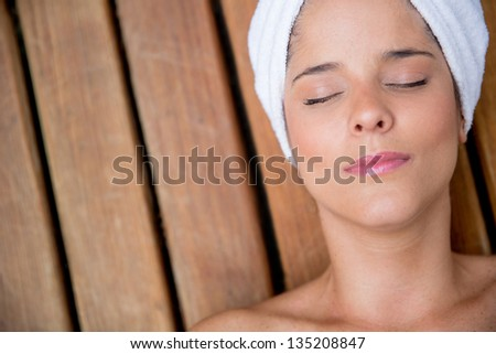 Relaxed woman at the spa enjoying a facial - stock photo