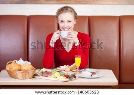 relaxed woman drinking cup of coffee at breakfast table in caf�© - stock photo