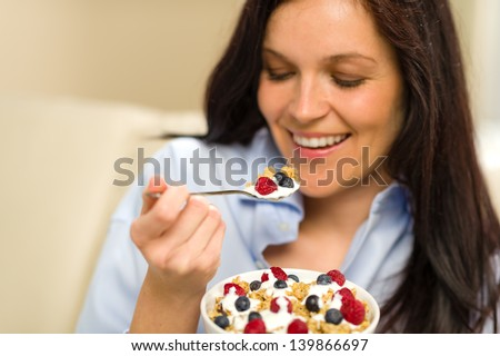 Relaxed woman eating bowl of cereal for breakfast - stock photo