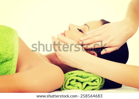 Relaxed woman enjoy receiving face massage at spa salon. - stock photo