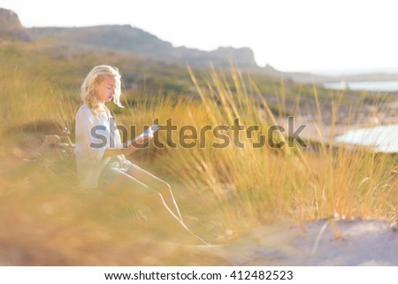 Relaxed woman enjoys reading on beautiful sandy beach.  Young lady with book in her hand. Concept of happiness, enjoyment and well being.  Enjoying Sun on Vacations.  - stock photo