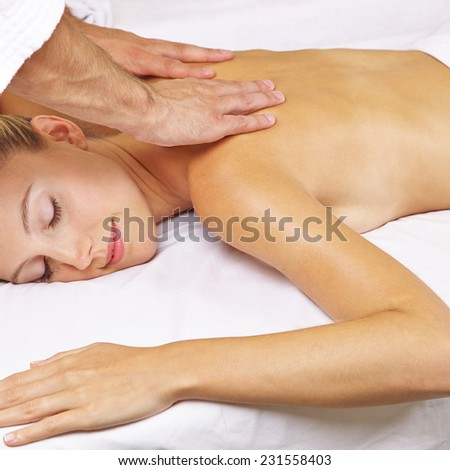 Relaxed woman getting thai massage for her back in a day spa - stock photo