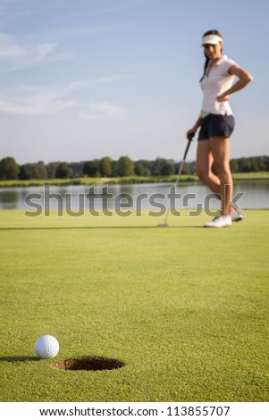 Relaxed woman golf player looking at ball that stopped near cup after putting on green. Focus on ball and hole. - stock photo