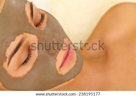 Relaxed woman having her face cleaned with clay mask - stock photo