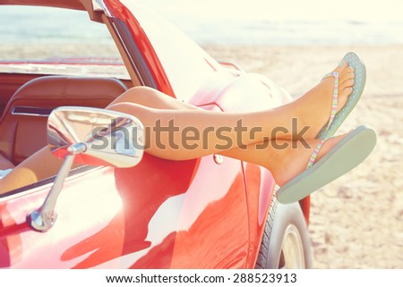 Relaxed woman legs and flip flops in a car window on the beach - stock photo