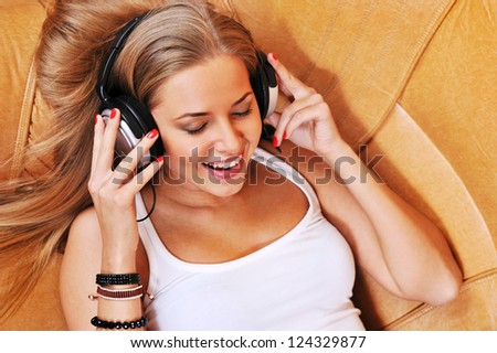 Relaxed woman listening to music in the living-room at home smiling with eyes closed - stock photo