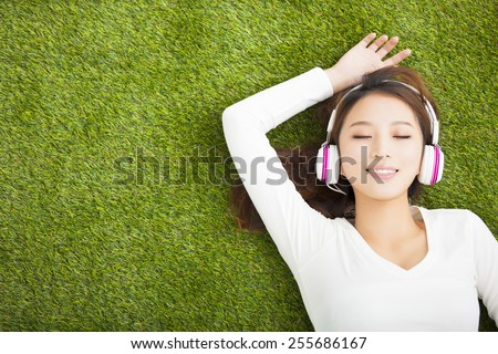 Relaxed woman listening to the music with headphones lying on the grass - stock photo