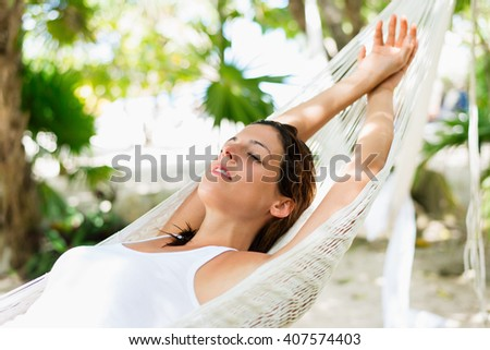 Relaxed woman napping on hammock. Relaxing tranquility on caribbean vacation. - stock photo