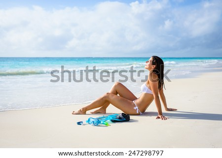 Relaxed woman on tropical beach vacation enjoying tranquility and resting after snorkeling. Brunette beautiful girl in white bikini relaxing and sunbathing. - stock photo