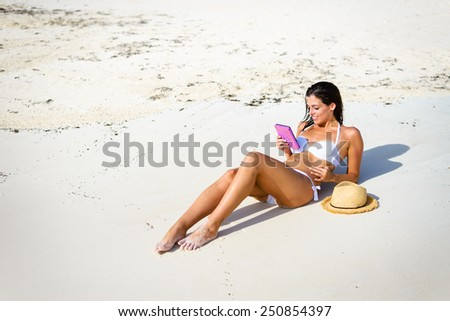 Relaxed woman reading a book at the beach during summer vacation. Young happy brunette lying on the sun with a e-book - stock photo
