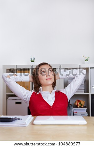 Relaxed woman sitting at her desk and looking up pensively - stock photo