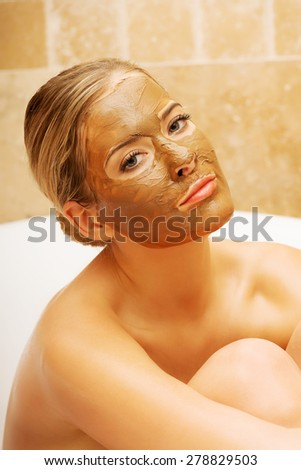 Relaxed woman sitting in a bath with face mask looking at the camera. - stock photo