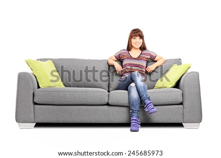Relaxed woman sitting on a modern sofa isolated on white background - stock photo