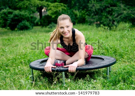 Relaxed woman sitting on mini trampoline - stock photo