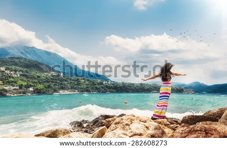 Relaxed woman with open arms from behind on sea. Girl from behind view enjoying in a summer day.  Copay space - copyspace - stock photo