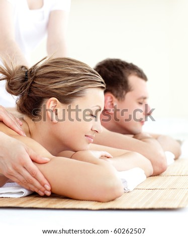 Relaxed young couple receiving a back massage in a spa center - stock photo