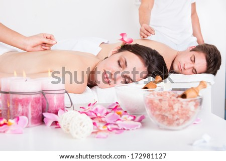 Relaxed Young Couple Receiving An Acupuncture Treatment In A Spa Center - stock photo