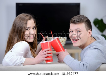 Relaxed young couple watching tv and drinking cola at home in bright living room - stock photo