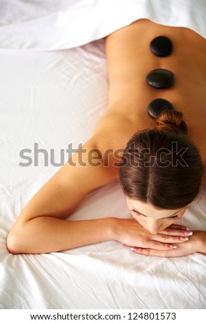 Relaxed young female getting a stone massage in a spa - stock photo