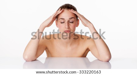 relaxed young female model with eyes closed massaging her face,leaning on white glass for lifting pampering treatment,studio shot,white background - stock photo