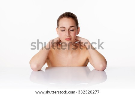 relaxed young female model with eyes closed massaging her neck,leaning on white glass for soft pampering treatment,studio shot,white background - stock photo
