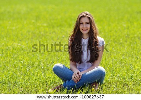 Relaxed young girl sitting on grass in park - Outdoor - stock photo