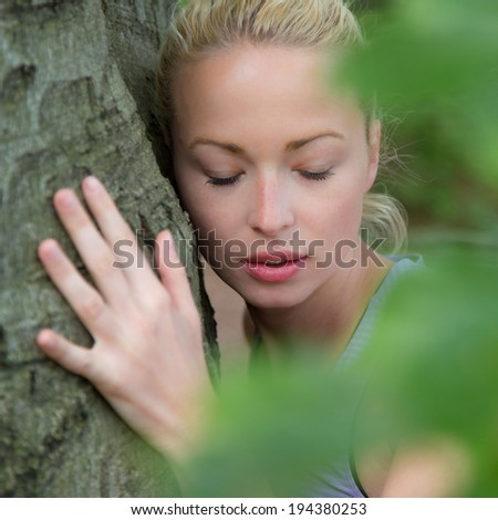 Relaxed young lady embracing a tree receiving life energy from the nature. - stock photo