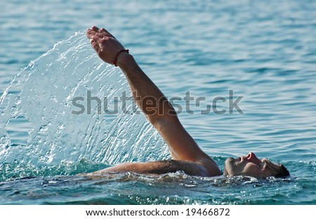 Relaxed young man swimming in a pure and clear sea water making nice water splashes. - stock photo