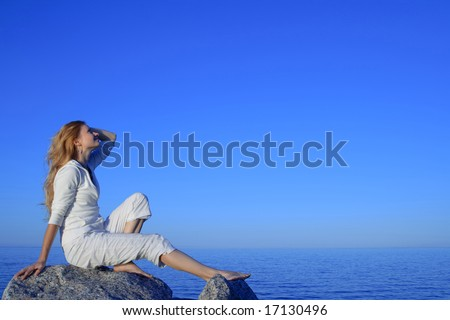 Relaxed young woman enjoying beautiful sunset by the sea. - stock photo