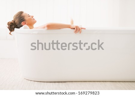 Relaxed young woman laying in bathtub - stock photo