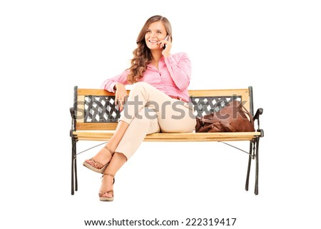 Relaxed young woman talking on the phone seated on a bench isolated on white background - stock photo