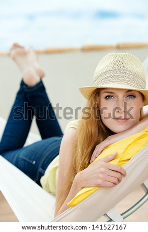 Relaxed young woman with sun hat daydreaming in hammock - stock photo