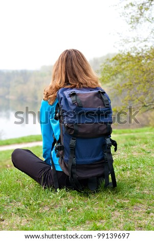 Relaxes woman tourist sitting on the grass. Back to us. Beautiful front view - stock photo