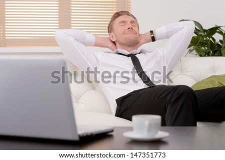 Relaxing after hard working day. Cheerful young businessman relaxing on the couch with his eyes closed - stock photo