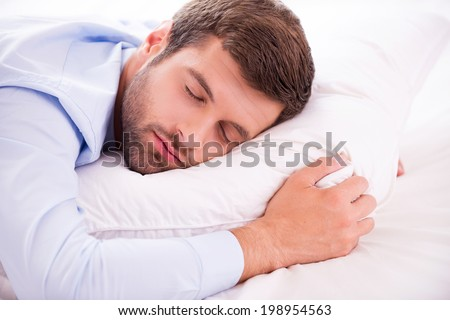 Relaxing after hard working day. Handsome young man in shirt and tie sleeping in bed  - stock photo