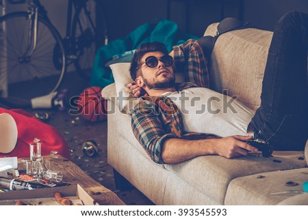 Relaxing after party. Young handsome man in sunglasses lying down on sofa with joystick in his hand in messy room after party - stock photo
