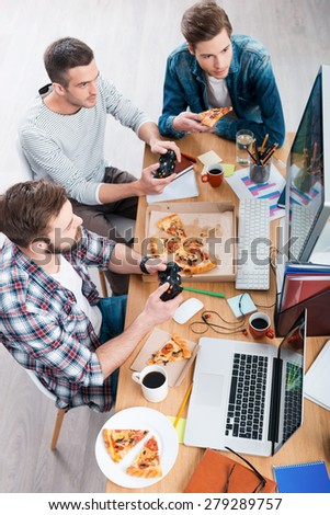 Relaxing after work. Top view of three young men playing computer games and eating pizza while sitting at the desk - stock photo