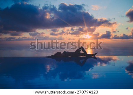 Relaxing at infinity pool - stock photo